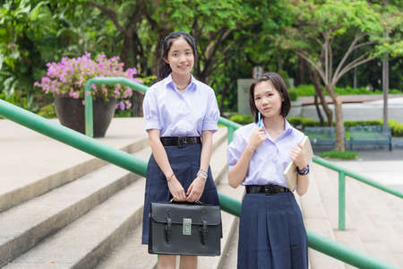 thai student: Cute Asian Thai high schoolgirls student couple in school uniform standing on the stairways with her friend looking toward in nature green background Stock Photo