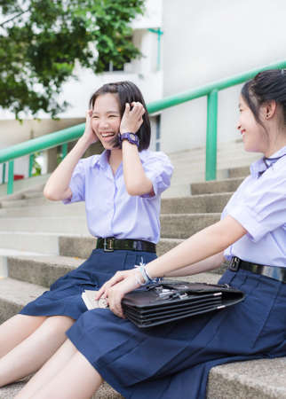 Cute Asian Thai high schoolgirls student in school uniform sit on the stairway showing a cute laugh while playing with her friend