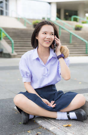 Cute Asian Thai high schoolgirl student in school uniform sitting and talking with her smart phone showing fun smiling happy facial expression