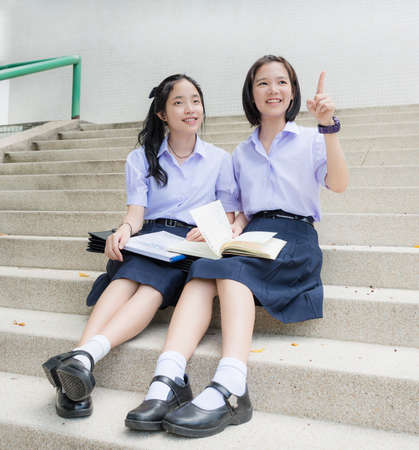 Cute Asian Thai high schoolgirls student couple in school uniform sit on the stairway pointing and looking at something in happy smiling face together on a building stairs