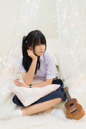 Cute Asian Thai high school girl in uniform with sitting with legs cross and a hand on the chin with pillow on her lap on white bed with furry blanket and decoration lights and guitar in schoolgirl fashion and recreation education concept.