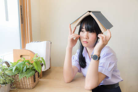 Cute Asian Thai high school girl in uniform with looking out of the window think of something else with book on her head with boredom in her room. Lazy schoolgirl in funny fashion and education concept.