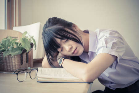 Shallow depth of field of cute Asian Thai high school girl in uniform fall asleep on the book on her dest during doing homework in fashion education concept in vintage color. Focus on arm and elbow and book. Stock Photo