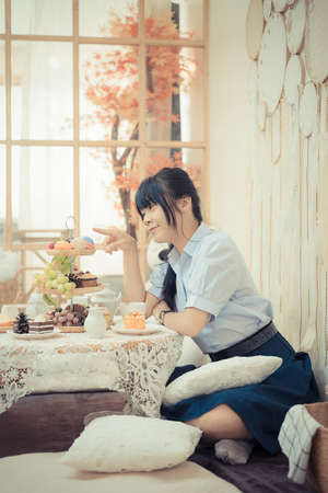 Cute Asian Thai high school girl in uniform is playing with dessert food decoration with various food fruit and candy in a lovely cafe or retaurant scene in vintage color style.