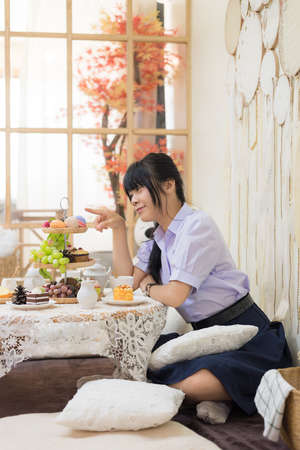 Cute Asian Thai high school girl in uniform is playing with dessert food decoration with various food fruit and candy in a lovely cafe or retaurant scene.