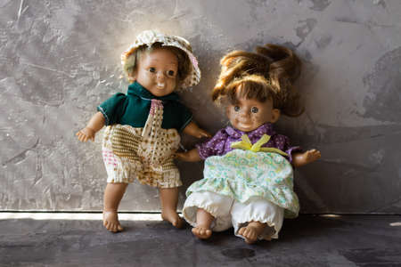 Ugly and scary dolls isolated in front of gray background.