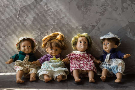 Ugly and scary dolls isolated in front of gray background. Фото со стока