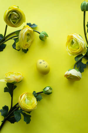 Happy Easter Day Around Yellow Flowers With Yellow Smiling Egg On a Yellow Background Stock Photo