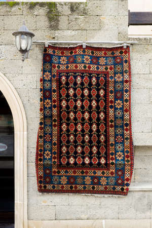 National carpets with Caucasian patterns are for sale in the old town on old stones