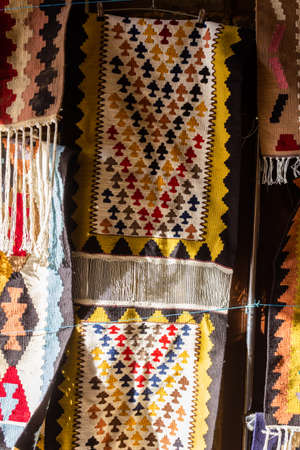 National carpets with Caucasian patterns are for sale in the old town on old stones Stock Photo