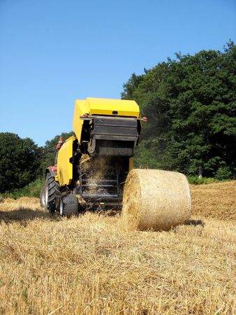 baler: Round baler with discharged wheat bale Stock Photo