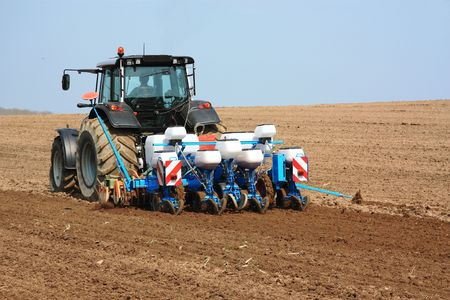 A tractor tows a planting and tilling unit during the planting of the spring crop.