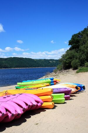 A row of colourful kayaks for hire to tourists on a beach with the water behind photo