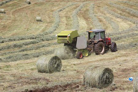 baler: A round baler discharging a round bale of hay Stock Photo