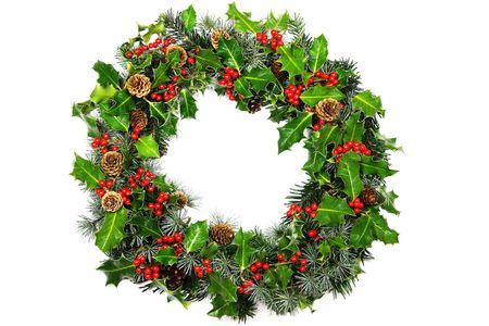 A Christmas holly wreath photographed over white with soft natural shadow