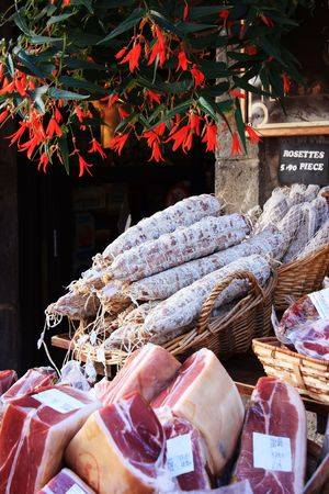 A typical  French open air street market selling cured meats such as rosette, coppa and hams Stock Photo