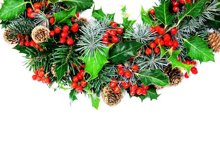 A traditional Christmas wreath of natural holly, pine, cypress and cones photographed over white - half wreath horizontal. photo