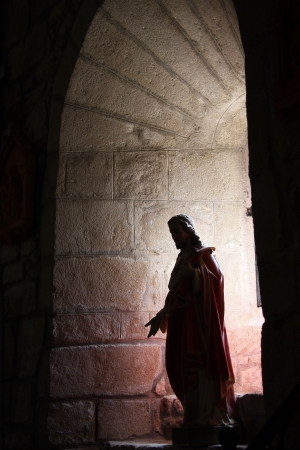 An ancient figure of Christ is silhoetted and backlit by sunlight through an arched granite alcove in a medieval chapel. Stock Photo