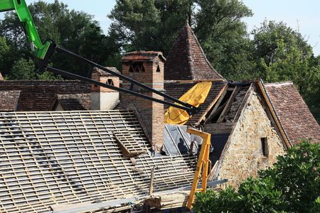waterproofing: Roof renovations to the tiled roof of an ancient 18thC rural dwelling showing materials suspended from the arm of a crane and new waterproofing and trusses. Stock Photo