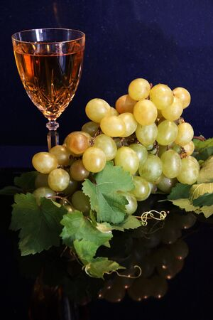 intoxicating: A festive still life of a glass of white wine with a bunch of white grapes against a darl blue marble backdrop.