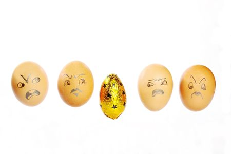 disapproving: A humorous Easter egg line up with four hens eggs with disapproving faces glaring at one foil wrapped Easter egg over white