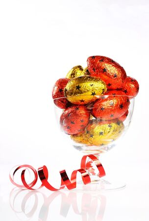 A glass dish of colourful red and gold foil wrapped Easter eggs with a coiled red ribbon over white