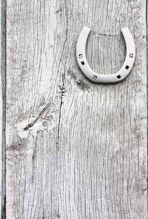 Lucky horse shoe on a grunge painted barn door. Stock Photo