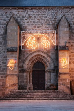 The entrance to an old stone church adorned with shining Christmas lights of the Nativity and angels photo