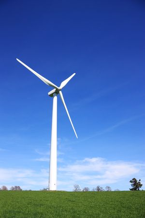 A wind turbine against a vivid blue sky on a green hilltop. photo