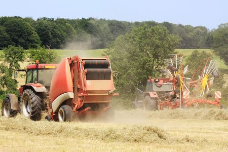 hay bale: Farmers use a circular rotational hay rake and baler to harvest  and bale the hay.