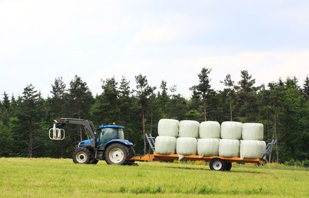 A farmer tows a trailer loaded with circular hay bales wrapped in white plastic behind a tractor
