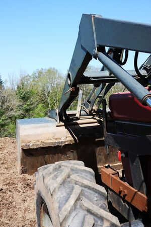 A close up of a farmer using a tractor and front end loader to move earth on a farm  Stock Photo