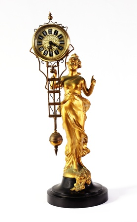 A genuine antique Art Nouveau gilt metal mystery clock with a robe clad woman holding up a pendulum clock with  slight oxidation and verdigris on the gilt metal Stock Photo