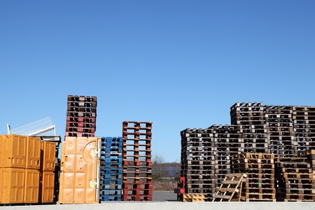 Stacks of wooden shipping and storage pallets and yellow plastic containers stand in an industrial yard for shipping and distribution of small cargo.