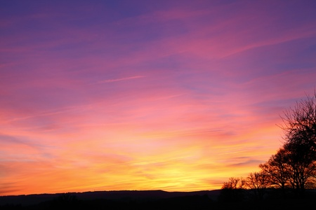 enhancement: A spectacular winter sunset with vivid colours of red and orange through purple, all natural colours without enhancement, over open countryside. Stock Photo