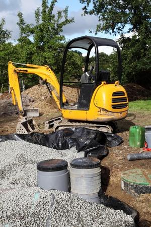 aguas residuales: Usando una miniexcavadora para instalar un filtro de arena y grava para su uso con un tanque séptico interno. Foto de archivo