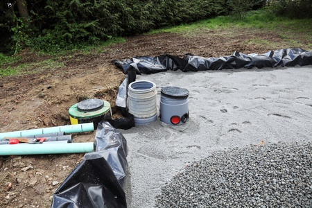 Installing a sand and gravel filter bed with filters and pump for a domestic septic tank system. Stock Photo