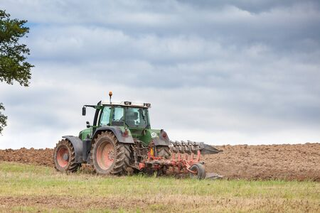 ploughing: Farmer ploughing overwintered fields ready for planting the spring crop with a tractor and plough