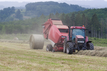 baler: Farmer baling hay in a misty mountain top pasture with a round hay bale exiting the baler. Mown and raked lines of dried grass. Surrounded by forests. Stock Photo