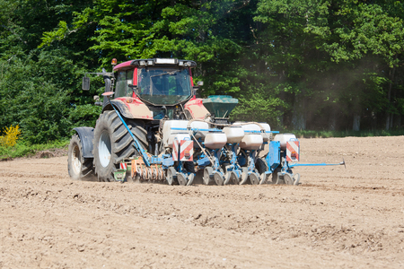 seed drill: Farmer using a mechanical planter and power harrow to prepare ploughed overwintered soil to drill and plant the seeds for the spring crop of maize for animal silage. Agricultural planter.