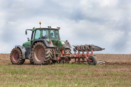 ploughing field: Farmer preparing an overwintered fallow field for planting the spring crop ploughing the land with a plough and tractor. Close up skyline view  against a cloudy sky Stock Photo
