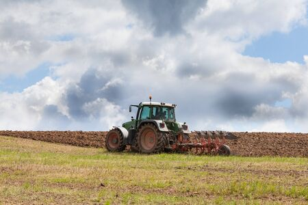 ploughing: Farmer ploughing an overwintered agricultural field on his farm with a tractor and plow ready for planting the new spring crop. Dramatic clouds in the background, tractor on skyline