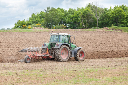 ploughing field: Farmer ploughing an overwintered agricultural  field ready for planting of the spring crops with a tractor and plough Stock Photo