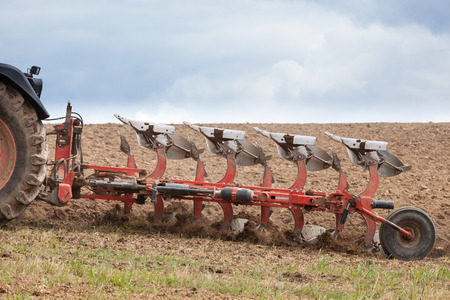 ploughing field: Close up detail of an agricultural plough in action ploughing an overwintered field in preparation for planting the spring crop