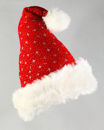 christmas hats: Colorful red Santa Hat with silver glitter stars to celebrate Christmas and the festive season isolated on a grey background