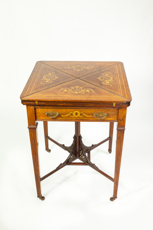 flaps: Inlaid late nineteenth century antique walnut and rosewood envelope card table with the flaps folded closed showing the marquetry with a single drawer in front on a white background