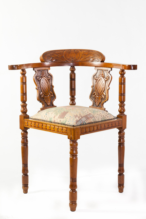 bygone: Antique 19th century fruitwood Captains chair or corner chair with an upholstered seat and handcarved detail over a white background Stock Photo