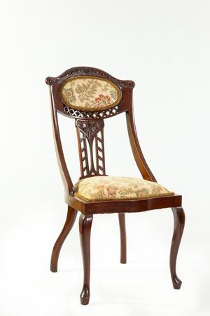 caoba: silla de salón de antigüedades de caoba de estilo Art Nouveau con un chorro de líneas curvas y elementos florales y frutales talladas, asiento tapizado y respaldo en un fondo blanco