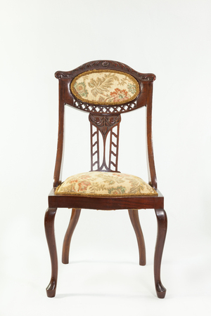 bygone: Front view of an antique Art Nouveau mahogany parlour chair with curved flowing lines and carved fruit and flower detail typical of the era over a white background Stock Photo