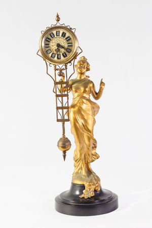 gilt: Gilt metal antique Art Nouveau pendulum clock of a lady in a  flowing dress holding the pendulum mechanism  with an ornate round dial in her hand over a white background